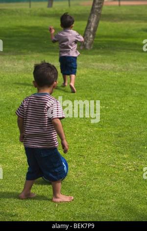 Due ragazzi che giocano a calcio in un parco Immagini Stock