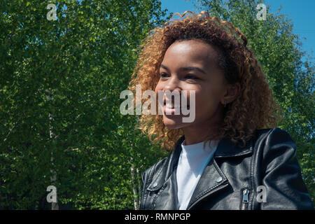 Una bella ragazza africana cammina per la strada in primavera Immagini Stock