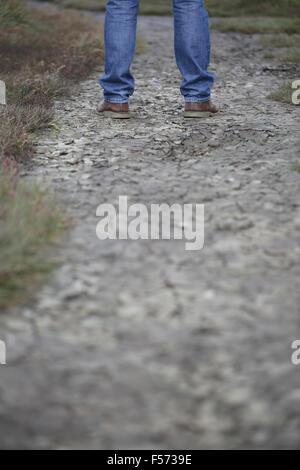 L uomo per le gambe in piedi sul suolo incrinato Immagini Stock