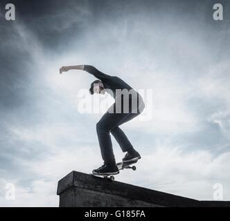 Giovane uomo lo skateboard su tetto Immagini Stock