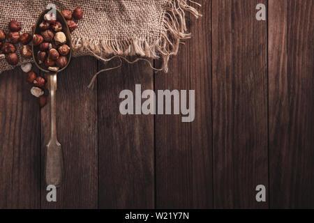 Le nocciole su un vecchio cucchiaio e composizione dal vecchio legno e materiale. Vista superiore e spazio vuoto sul lato destro per il testo Immagini Stock