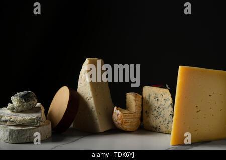 Una selezione di formaggi su un marmo la superficie della piastrella. Immagini Stock