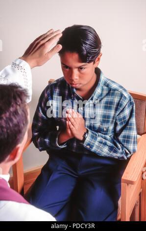 Ragazzo adolescente nella riconciliazione con sacerdote © Myrleen Pearson ....Ferguson Cate Immagini Stock