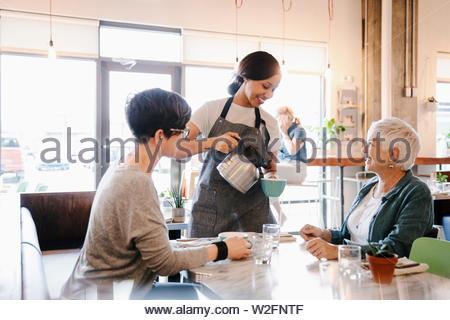 Cameriera versando il caffè per la madre e la figlia in cafe Immagini Stock