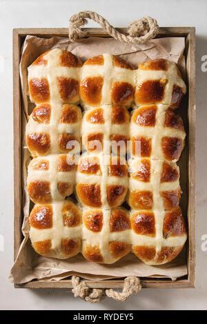 Pasqua in casa calde tradizionali ciambelle a croce in legno vassoio vassoio con carta da forno su marmo bianco dello sfondo. Vista superiore, spazio Immagini Stock