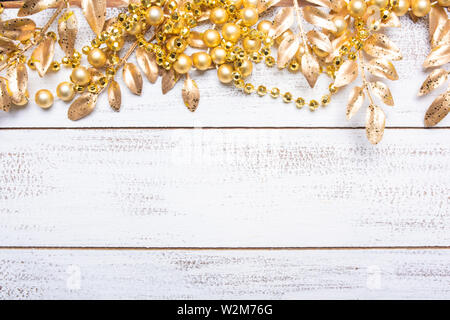 Golden colorate decorazioni di Natale su un bianco sullo sfondo di legno con copia spazio. Foglie, garland, bacche etc. Immagini Stock