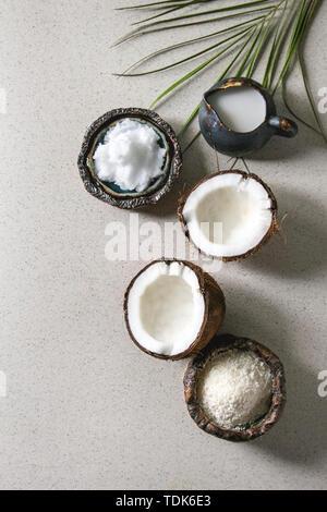 Varietà di prodotti di cocco il latte nel bricco, olio e scaglie di coppe in ceramica, fresche noce di cocco rotto su grigio maculato sfondo. Mangiare sano. Piatto, laici s Immagini Stock
