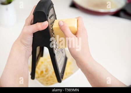 Griglie di donna il formaggio su una grattugia in cucina. Immagini Stock