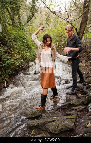 Donna camminano attraverso creek con l'uomo dietro di lei. Immagini Stock