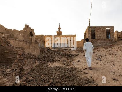 I sudanesi man walking thru il abandonned mudbrick case, Stato settentrionale, Al-Khandaq, Sudan Immagini Stock