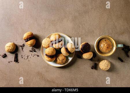 Baci di dama casalingo italiano biscotti di nocciole biscotti con crema di cioccolato servita nella piastra in ceramica con tazza di caffè espresso su texture marrone ba Immagini Stock