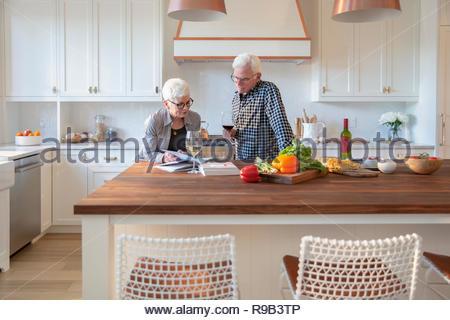 Coppia senior per la cottura, bere vino e la lettura di libri di cucina in cucina Immagini Stock