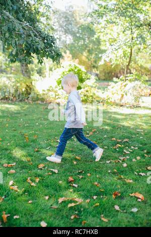 Ragazzo camminando su erba nel parco Immagini Stock