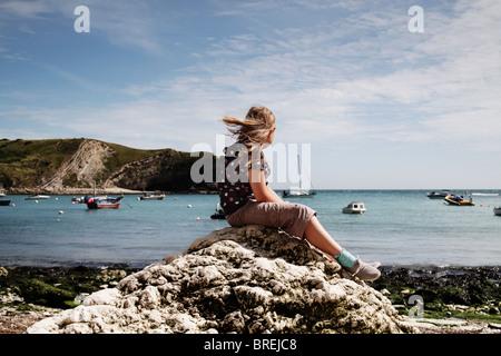 Ragazza seduta su di una roccia a Lulworth Cove,UK Immagini Stock