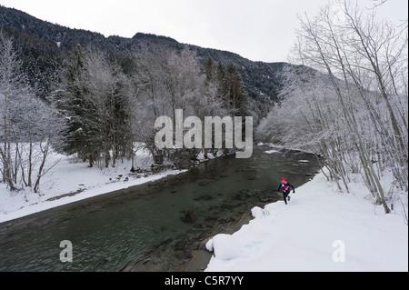 Un runner jogging lungo un fiume nevoso. Immagini Stock
