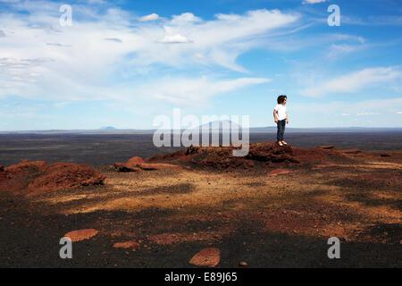 Ragazzo in piedi sulle rocce a crateri della luna Immagini Stock