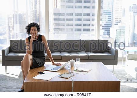 Ritratto fiducioso e sorridente imprenditrice lavorando in ufficio urbano lounge Immagini Stock