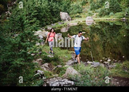 Escursionismo coppia lungo il lago nei boschi Immagini Stock