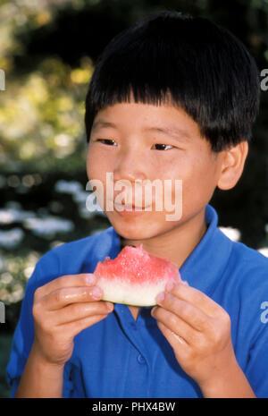 Giovane ragazzo coreano mangiando anguria fuori © Myrleen Pearson ..Ferguson Cate Immagini Stock