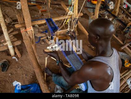 L'uomo africano tessitura in un tradizionale fabbrica tessile, Savanes distretto, Waraniene, Costa d'Avorio Immagini Stock