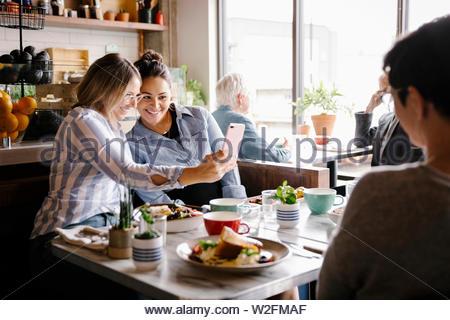 Le donne amici prendendo selfie con la fotocamera del telefono in cafe Immagini Stock