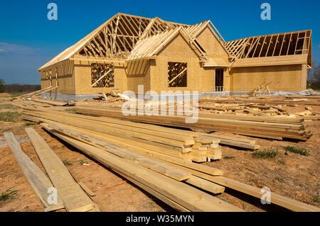 Una casa in costruzione con legno e materiali di consumo Immagini Stock