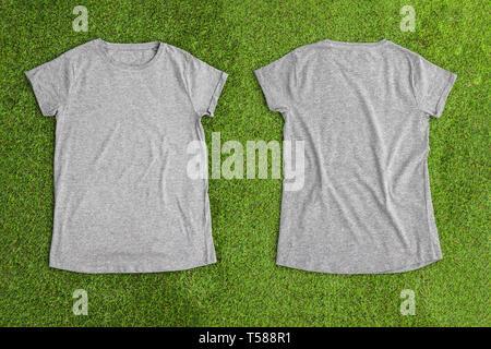Parte anteriore e posteriore del grigio melange svuotare T-shirt su sfondo di erba. Vista orizzontale. Immagini Stock