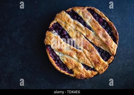 Torta di ciliegie con un reticolo e crosta di scaglie shot su sfondo blu Immagini Stock