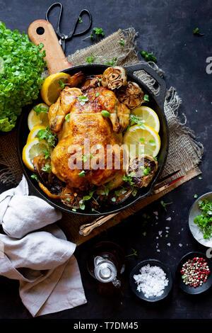 Intero pollo arrostito in una ghisa pan Immagini Stock