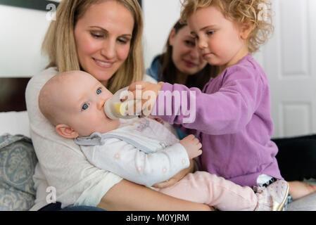 Ragazza caucasica biberon per baby sorella Immagini Stock