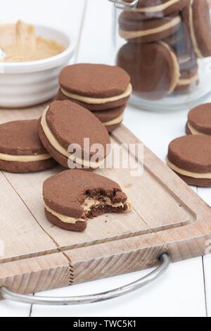 Cioccolato artigianale di burro di arachidi frollini dolci il. Cioccolato rotondo di biscotti frollini con burro di arachidi crema nel mezzo Immagini Stock