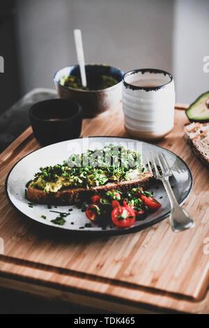 Vegano sani in estate la colazione. Avocado tostare il pane a lievitazione naturale con erba cipollina, coriandolo e pomodori ciliegie, con tazza di caffè sulla tavola di legno. Vegeta Immagini Stock