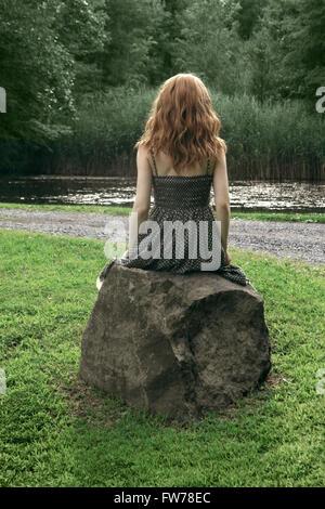 Vista posteriore di una giovane donna in polka dot dress seduto su una roccia Immagini Stock