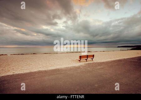 Banco vuoto in spiaggia Immagini Stock
