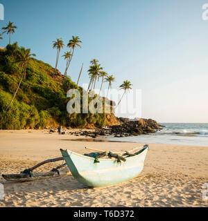 Barca di legno tradizionale Talalla sulla spiaggia al tramonto, South Coast, Sri Lanka, Asia Immagini Stock