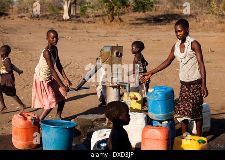 In Africa i bambini il pompaggio di acqua in un tubo di supporto Immagini Stock