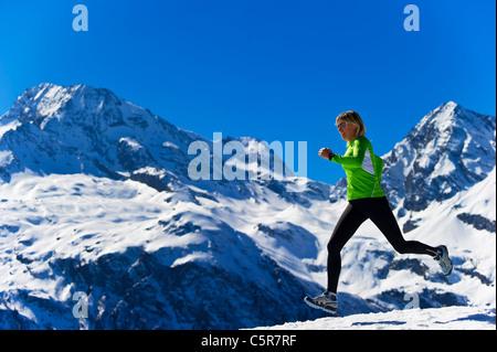Una donna jogging attraverso innevate montagne alpine. Immagini Stock