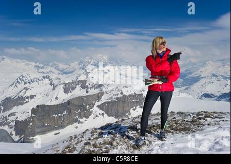 Una donna orienteering in alta quota sulle montagne. Immagini Stock