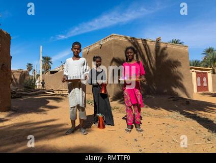 Bambini sudanesi tè offrendo ai visitatori in un villaggio, Stato settentrionale, Karima, Sudan Immagini Stock