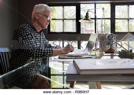 Senior uomo utilizzando laptop in home office Immagini Stock