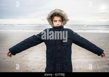 Un giovane ragazzo che sta sulla spiaggia di Porthmadog. Immagini Stock