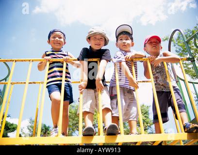 Quattro ragazzi a attrezzature da gioco nel parco Immagini Stock
