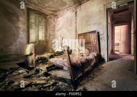 Vista interna di una camera da letto in un hotel abbandonato in Italia. Immagini Stock