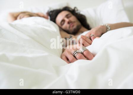 Raffreddare una coppia giovane relax nel letto con gli occhi chiusi. Immagini Stock