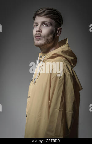 Ritratto in studio di un barbuto giovane in un giallo giacca a vento. Immagini Stock