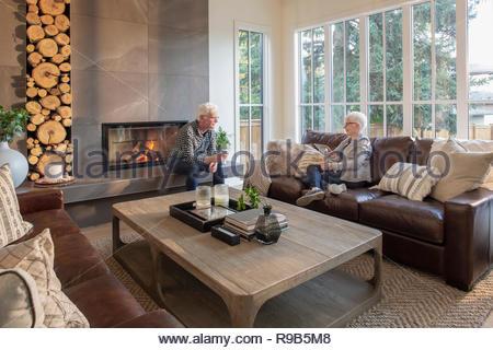 Coppia senior rilassante, bere vino e parlare nella stanza vivente Immagini Stock
