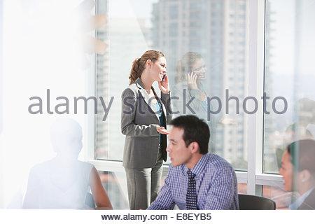 Imprenditrice parlando al cellulare in riunione Immagini Stock