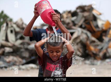 La striscia di Gaza. 17 Luglio, 2019. Un bambino palestinese è versata con acqua per rimanere fresco durante la stagione calda, nel sud della striscia di Gaza city di Khan Younis, 17 luglio 2019. Credito: Yasser Qudih/Xinhua/Alamy Live News Immagini Stock