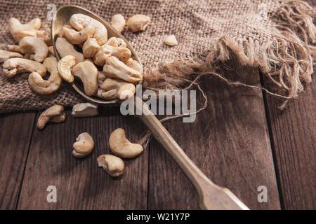 Noci di acagiù su un vecchio cucchiaio e composizione dal vecchio legno e materiali Immagini Stock