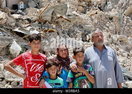 (190717) -- di Mosul, luglio 17, 2019 (Xinhua) -- Laith Najim (1R) e i suoi familiari a stare di fronte al loro prossimo la casa distrutta nella vecchia città di Mosul, Iraq, luglio 14, 2019. La guerra per liberare l Iraq di Mosul da uno Stato islamico (SI) gruppo militante ha ottenuto la vittoria per due anni, ma le sue gravi impatti ancora pesare sui residenti della città. Un grassroots campagna di raccolta fondi è stato avviato in cinese social media con schiacciante solidarietà, puntando a portare speranza alla guerra-ridden famiglie in Iraq di Mosul. Per andare con 'Funzione: Cinese grassroots donazioni portare speranza a w Immagini Stock
